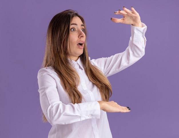 충격을 받은 젊고 예쁜 백인 소녀는 복사 공간이 있는 보라색 벽에 고립된 무언가를 들고 있는 척 손을 벌리고 있습니다