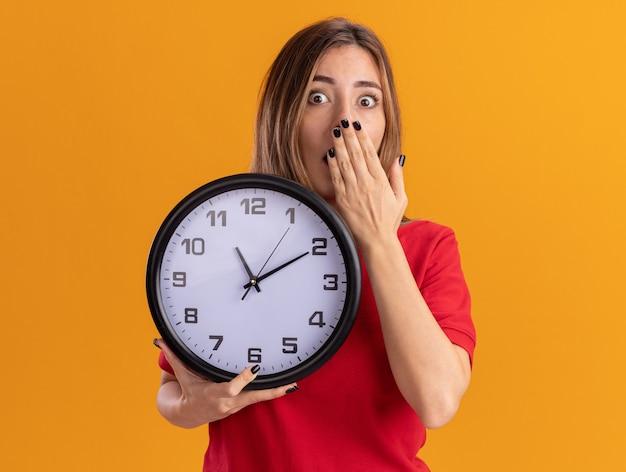 La giovane ragazza abbastanza caucasica scioccata mette la mano sulla bocca e tiene l'orologio sull'arancia