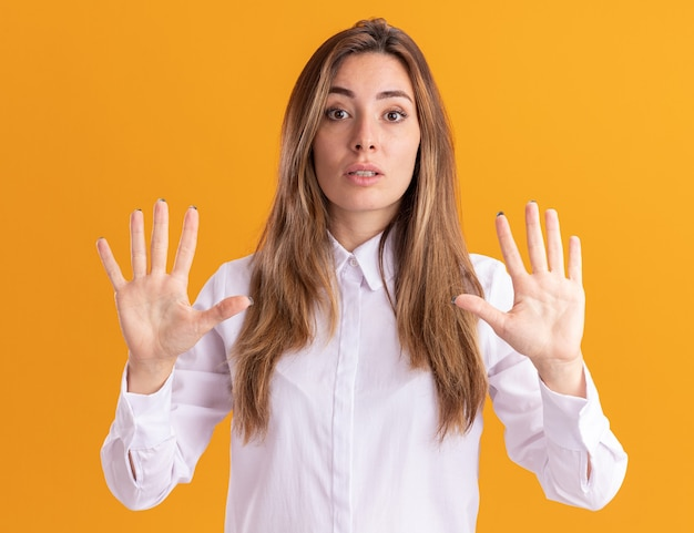 Shocked young pretty caucasian girl stands with raised hands