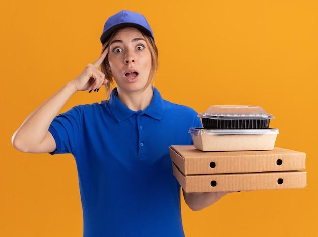La giovane ragazza graziosa di consegna scioccata in uniforme mette il dito sul tempio e tiene i pacchetti di cibo di carta