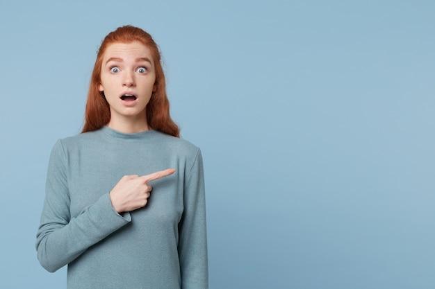 파란색 벽에 빈 복사본 공간에 오른쪽을 가리키는 충격 된 젊은 꽤 나가서는 젊은 여자