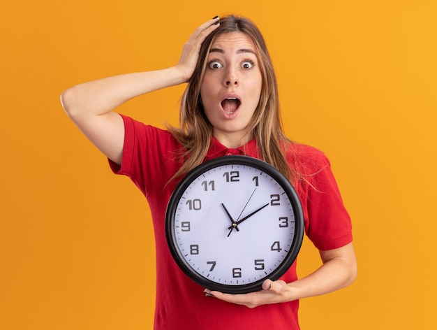 충격을받은 젊은 예쁜 여자가 머리에 손을 넣고 오렌지 벽에 고립 된 시계를 보유하고 있습니다.