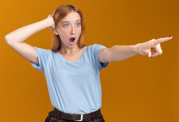 Scioccato giovane ragazza rossa zenzero con lentiggini mette la mano sulla testa guardando e indicando a lato
