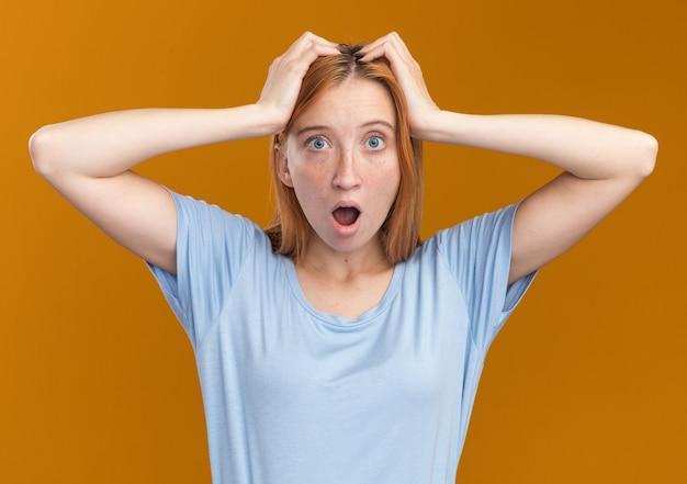 주근깨가있는 충격을받은 젊은 빨간 머리 생강 소녀가 머리에 손을 대고 오렌지색에 카메라를 봅니다.