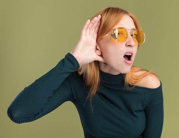 Scioccato giovane ragazza rossa zenzero con lentiggini in occhiali da sole tenendo la mano dietro l'orecchio isolato sulla parete verde oliva con copia spazio