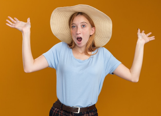 Shocked young redhead ginger girl with freckles wearing beach hat standing with raised hands