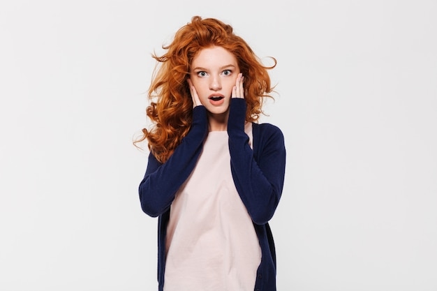 Shocked young redhead lady standing isolated