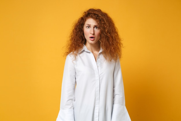 Shocked young redhead woman girl in casual white shirt posing isolated on yellow orange wall