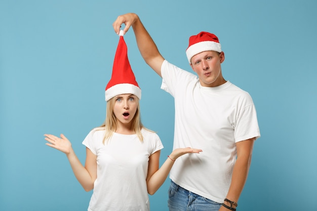 クリスマスの帽子のポーズでショックを受けた若いサンタカップルの友人の男と女