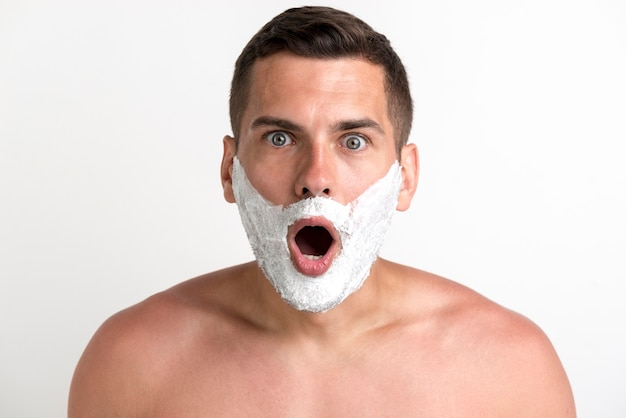 Shocked young shirtless man applied shaving cream looking at camera
