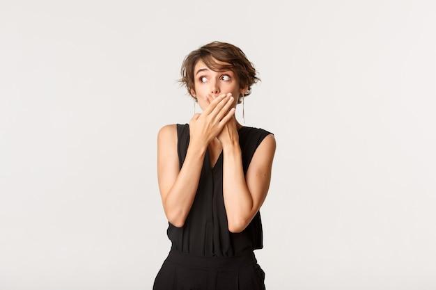 Потрясенная молодая глупая девушка сплетничает, задыхается и прикрывает рот изумленным,