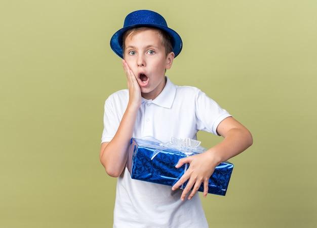 彼の顔に手を置き、コピースペースでオリーブグリーンの壁に隔離されたギフトボックスを保持している青いパーティーハットでショックを受けた若いスラブ少年