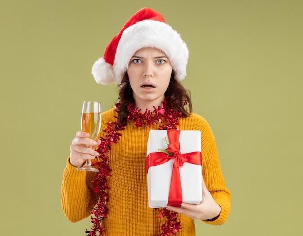 サンタの帽子と首の周りに花輪を持つショックを受けた若いスラブの女の子は、コピースペースのあるオリーブグリーンの壁に隔離されたシャンパンとクリスマスギフトボックスのガラスを保持しています