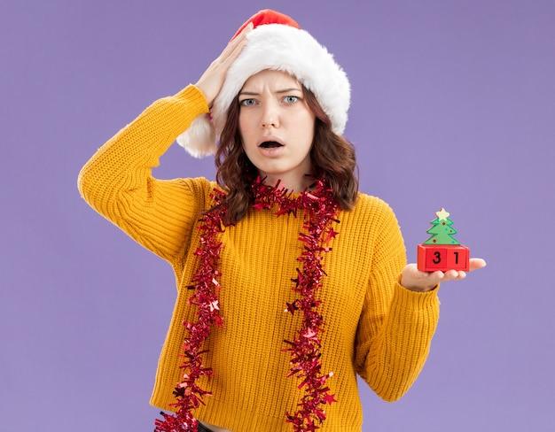 サンタの帽子と首に花輪を持つショックを受けた若いスラブの女の子は頭に手を置き、コピースペースで紫色の背景に分離されたクリスマスツリーの飾りを保持します。