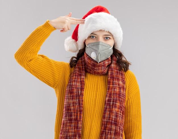 산타 모자와 총 제스처를 하 고 복사 공간 흰색 배경에 고립 된 그녀의 사원에 넣어 의료 마스크를 착용하는 목에 스카프와 충격 된 젊은 슬라브 소녀