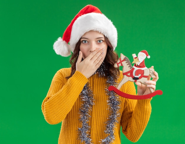 Shocked young slavic girl with santa hat and with garland around neck puts hand on mouth and holds santa on rocking horse decoration
