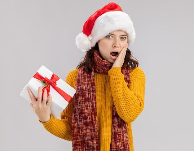 Scioccato giovane ragazza slava con cappello da babbo natale e con sciarpa intorno al collo mette la mano sul viso e tiene la scatola regalo di natale isolata sul muro bianco con spazio di copia