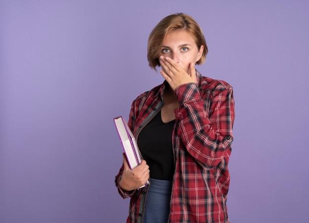 충격을받은 젊은 슬라브 학생 소녀가 책을 들고 노트북이 입에 손을 넣습니다.