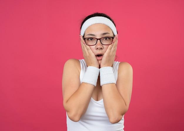 머리띠와 팔찌를 착용하는 광학 안경에 충격을받은 젊은 스포티 한 소녀가 얼굴에 손을 넣습니다.