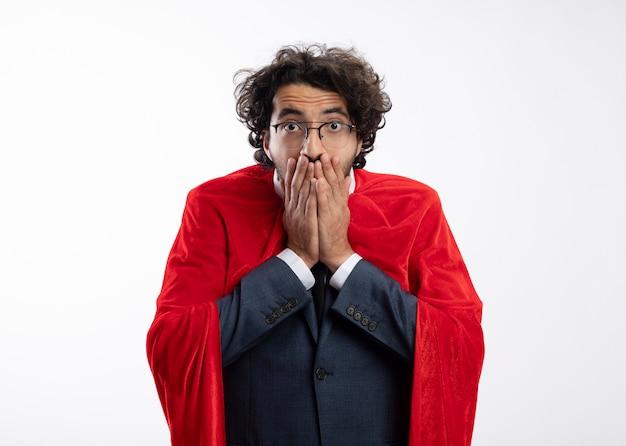 Scioccato giovane supereroe in vetri ottici che indossa tuta con mantello rosso mette le mani sulla bocca isolata sul muro bianco