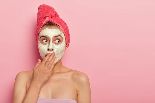 충격을받은 젊은 여성이 점토 영양 페이셜 마스크를 바르고, 손바닥으로 입을 가리고, 수분을 공급하고, 피부를 진정시키고, 머리에 싸인 장미 빛 수건을 착용하고, 분홍색 벽에 서 있습니다. 회춘 개념