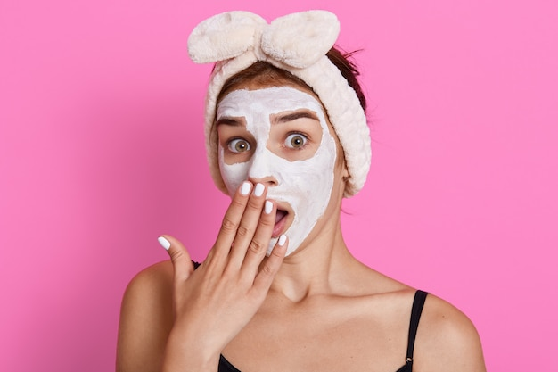 Shocked young woman applies clay nourishing facial mask, covers mouth with palm, wearing hairband, stands against pink wall, female doing rejuvenation procedures.