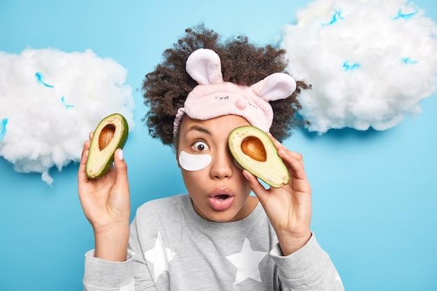 La giovane donna scioccata copre gli occhi con metà di avocado utilizza prodotti biologici e cosmetici naturali applica patch sotto gli occhi indossa pigiama sleepmask pone contro il muro blu