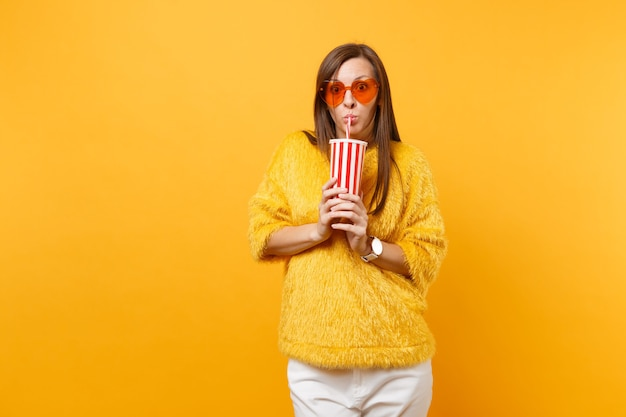 Shocked young woman in fur sweater and heart orange glasses drinking cola or soda from plastic cup isolated on bright yellow background. people sincere emotions, lifestyle concept. advertising area.