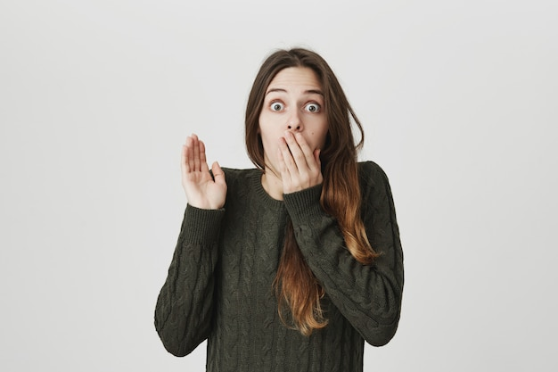 Shocked young woman gasping, raise arm