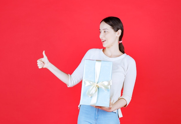Giovane donna scioccata che tiene in mano una confezione regalo e fa un gesto con il pollice in su