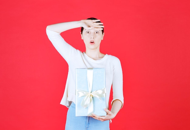 Shocked young woman holding gift box and put her hands to her forehead
