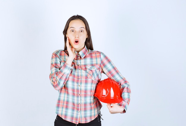 Shocked young woman holding red helmet on white background.