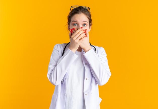 청진기가 입에 손을 대고 의사 제복을 입은 충격된 젊은 여성