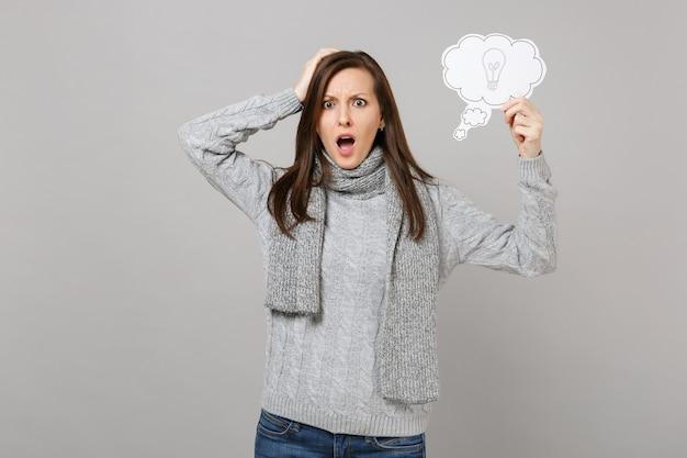 회색 스웨터를 입은 젊은 여성에게 충격을 받은 스카프는 머리에 손을 얹고 회색 벽 배경에 전구가 분리된 구름을 들고 있습니다. 건강한 패션 라이프스타일, 사람들의 진심 어린 감정, 추운 계절 개념.