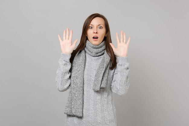 회색 스웨터 스카프를 두른 젊은 여성이 손을 들고 스튜디오의 회색 배경에 격리된 손바닥을 보여줍니다. 건강한 패션 라이프 스타일, 사람들은 진심 어린 감정 추운 계절 개념입니다. 복사 공간을 비웃습니다.