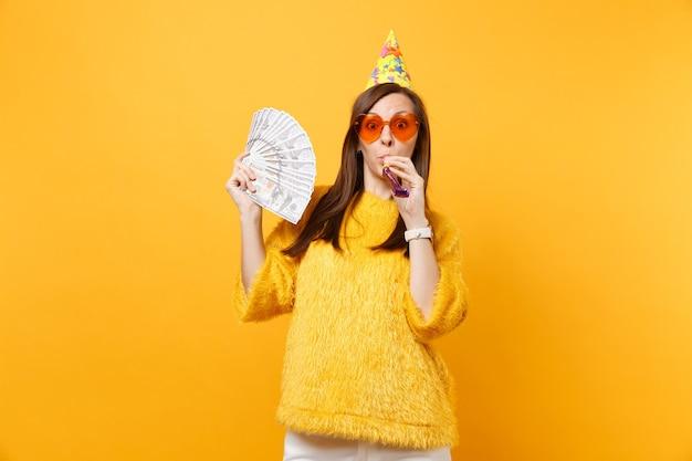 Шокированная молодая женщина в оранжевых очках сердца, шляпе дня рождения с игральной трубой, держащей пачку много долларов, празднование наличных денег на желтом фоне. люди искренние эмоции, образ жизни.