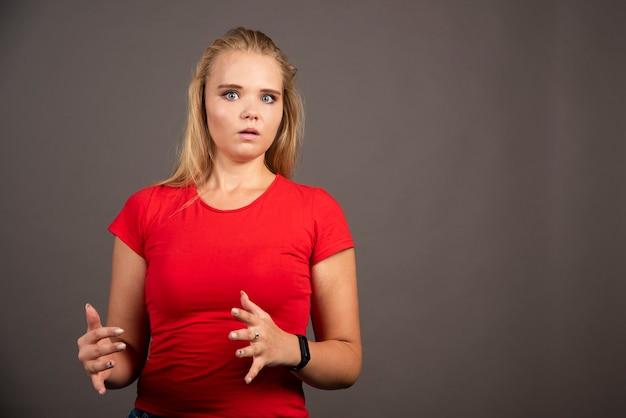 黒い壁に赤いシャツを着てショックを受けた若い女性。
