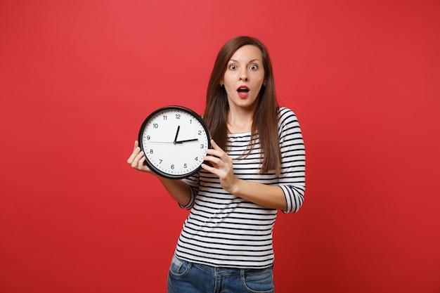 Шокированная молодая женщина в полосатой одежде держит рот широко открытым, выглядит удивленным, держит круглые часы, изолированные на ярко-красном фоне. концепция образа жизни искренние эмоции людей. копируйте пространство для копирования.