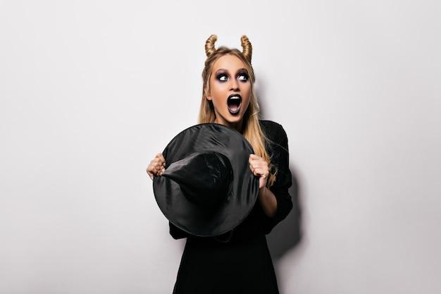 Шокированная молодая женщина в костюме вампира, стоящая на белой стене с открытым ртом. фотография в помещении элегантной дамы, празднующей хэллоуин.