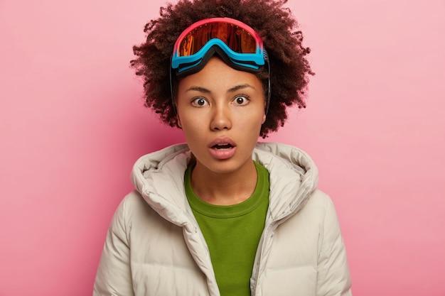 Шокированная молодая женщина в зимней одежде, носит маску для сноубординга на голове, задерживает дыхание от чуда, изолирована на розовом фоне