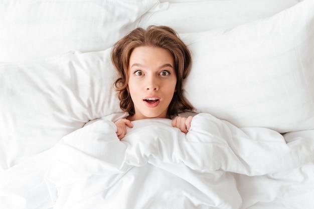 Шокированная молодая женщина лежит в постели утром