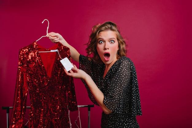 Giovane donna scioccata che esamina il cartellino del prezzo sul vestito rosso