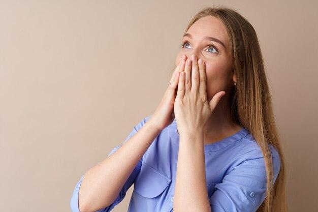 Шокированная молодая женщина смотрит вверх и прикрывает рот руками