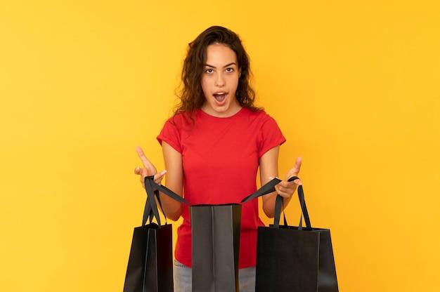 Потрясенная молодая женщина открыла черную сумку для покупок.