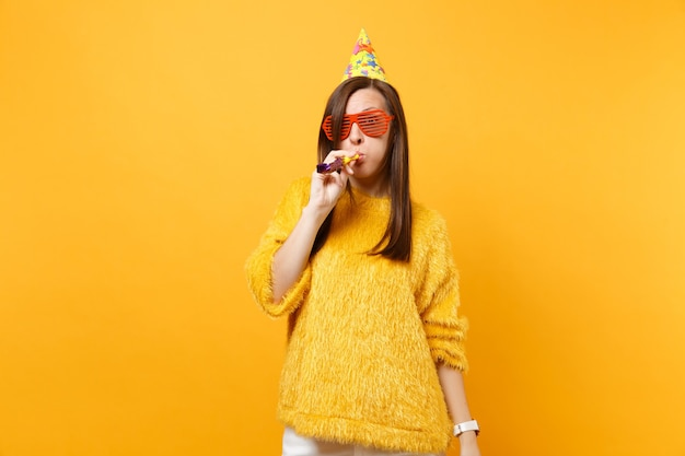 Shocked young woman in orange funny eyeglasses, birthday party hat with playing pipe celebrating isolated on bright yellow background. people sincere emotions, lifestyle concept. advertising area.