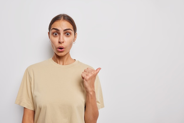 La giovane donna scioccata punta il pollice lontano mostra la vendita speciale o lo sconto sul prezzo mantiene la mascella caduta indossa una maglietta beige casual isolata sul muro bianco impressionato per parlare dell'offerta promozionale