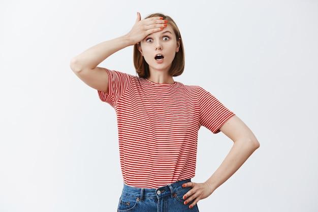 ショックを受けた若い女性は額をパンチし、あえぎ驚いた