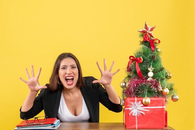 노란색 사무실에서 장식 된 크리스마스 트리 근처 테이블에 앉아 10을 보여주는 충격 된 젊은 여자