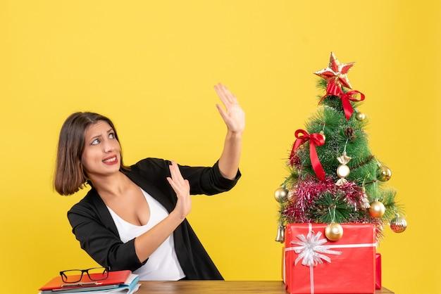 Шокированная молодая женщина показывает десять сидящих за столом возле украшенной рождественской елки в офисе на желтом