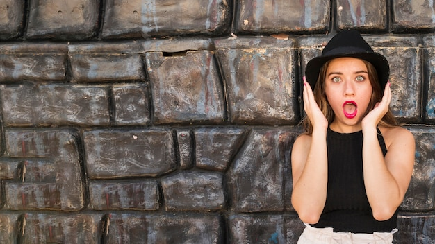 Shocked young woman standing against wall